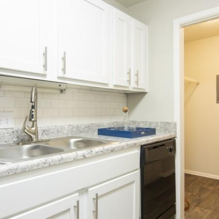 View into kitchen with white cabinets, upgraded countertops and stainless double stink with upgraded faucet