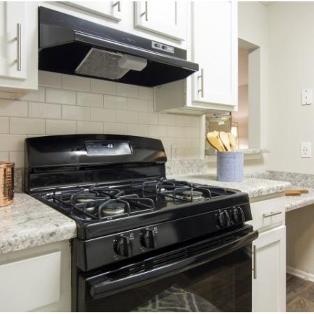 View into kitchen with white cabinets, upgraded countertops and black appliances