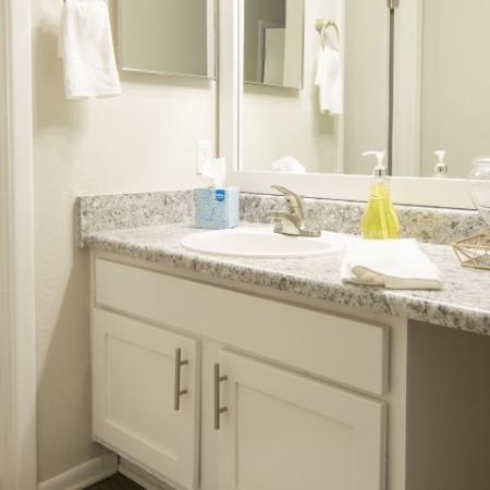 Bathroom with white shaker style cabinets, upgraded countertops and framed mirror