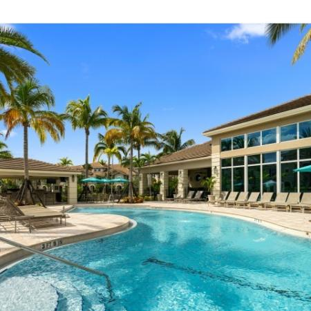 Pool surrounded by lounge chairs and palm trees in front of club house with floor to ceiling windows