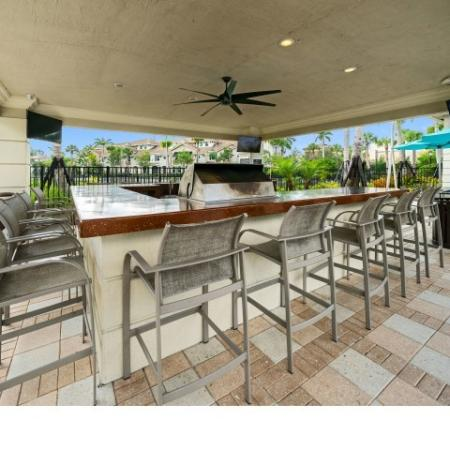 Outdoor bar with grille with three televisions and a ceiling fan