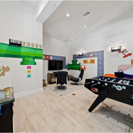 Game room with video game wall art, foosball table, video games and console lounge