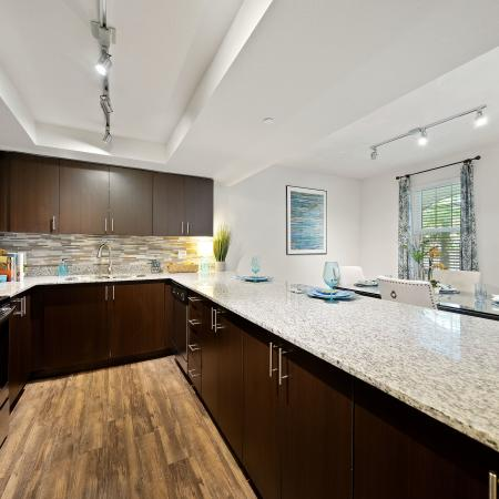 Kitchen with tile back splash and stainless steel refrigerator and oven overlooking dining room