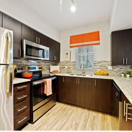 Kitchen with back splash and stainless steel refrigerator, microwave, and oven