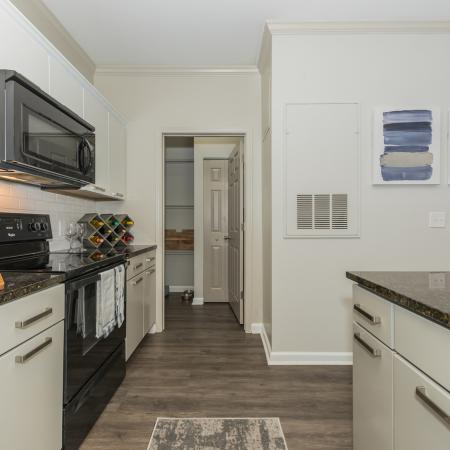 Apartment interior kitchen with wood inspired plank flooring , white shaker style cabinet and black appliances