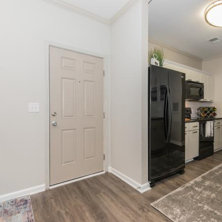 Entry way and kitchen view with black appliances, wood inspired flooring, modern lighting
