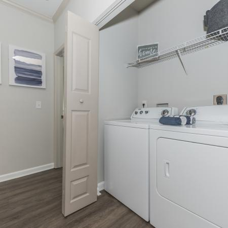 Full sized washer and dryer closet with wire rack and wood flooring