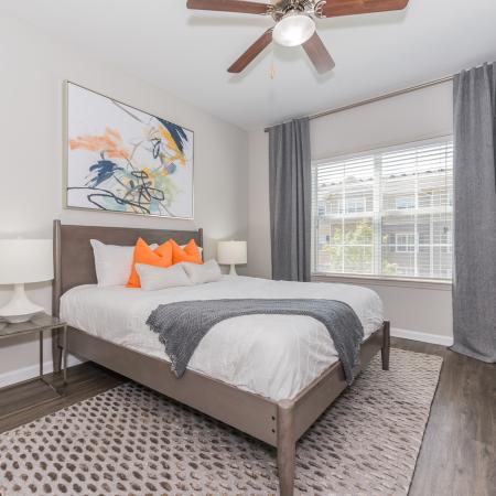 Bedroom with double windows, wood inspired flooring and ceiling fan with light fixture