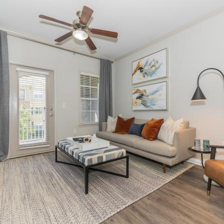 Spacious living room, ,modern couch and chair, large window and back patio door with ceiling fan with light