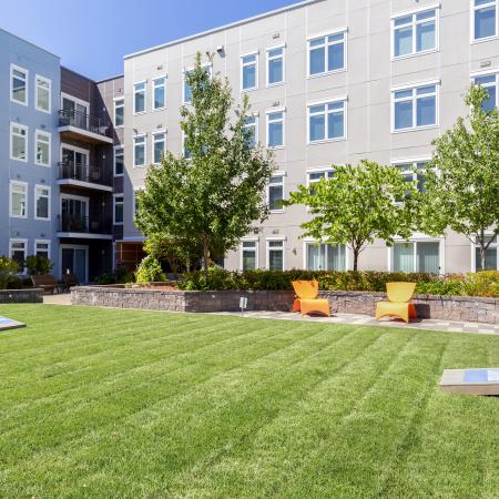 Manicured elevated lawn with cornhole and seating. Landscaped pathway with trees in background