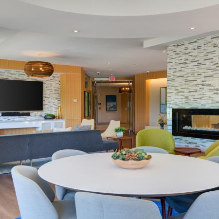 View of clubroom from behind six person round table towards sectional sofa and wall mounted TV. Fireplace with two additional lime green chairs sit in front and to the right.
