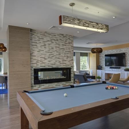 View of resident lounge behind pool table with blue felt top with fireplace in front. Large wall mounted TV and seating can be seen to the right and tables and chairs with large windows are to the left.