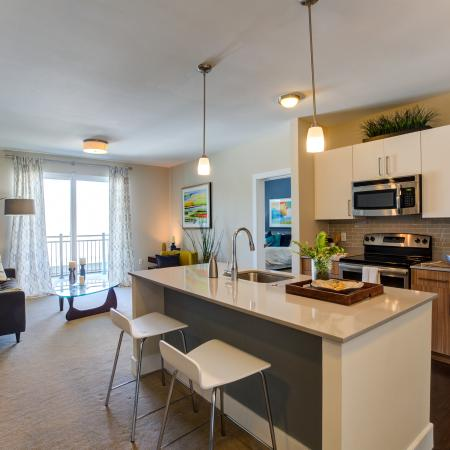 View of kitchen with living room and balcony in background. Kitchen features island with stools in front. Two-tone cabinets with white upper cabinets and wood pattern lower cabinets. Stainless steel refrigerator, stove and microwave.