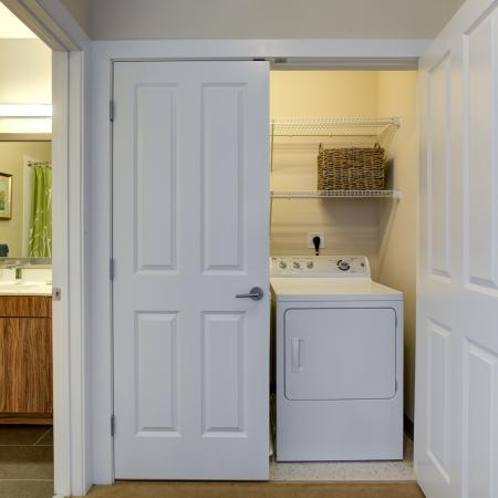 Bathroom vanity with wood patterned cabinets below vanity and silver framed mirror hung above seen to left. Laundry room with one door closed and one door open showing white dryer and two shelves for storage above is on the right.