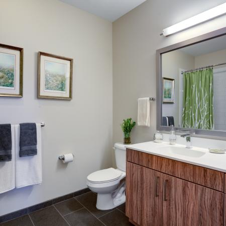 Extra long white vanity countertop with sink and wood patterned cabinet plus drawers below counter. Oversized silver framed mirror hung above vanity with toilet positioned to the left. Tile flooring and towel rod with art hung above.