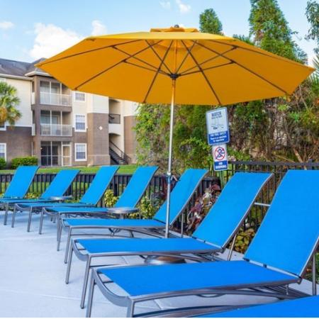 Alvista Sterling Palms outdoor pool deck with lawn chairs and market umbrellas