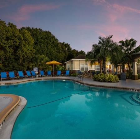 Alvista Sterling Palms sparkling swimming pool with lawn chairs and market umbrellas at twilight