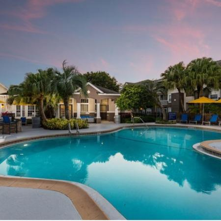 Alvista Sterling Palms swimming pool with lawn chairs and market umbrellas as twilight