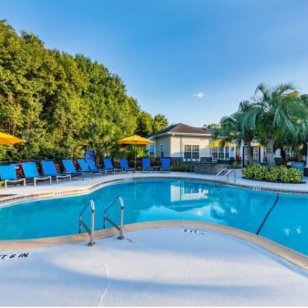 Alvista Sterling Palms sparkling swimming pool with lawn chairs and market umbrellas