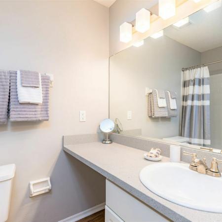 Furnished model bathroom vanity area with bath decor