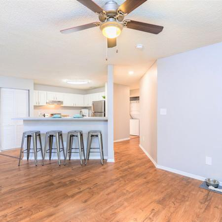 Looking into apartment kitchen breakfast bar with barstools from living room area