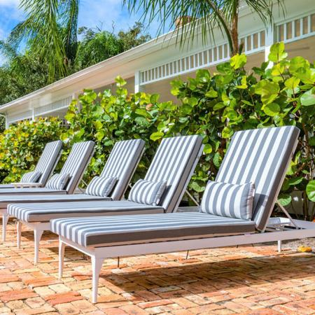 Pool lounge chairs lined up in a row