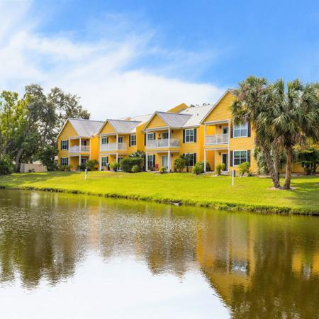 View of apartment building exteriors and pond