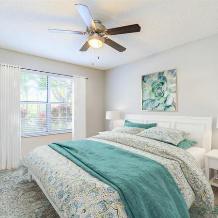 Furnished model bedroom with bed, nightstands and ceiling fan
