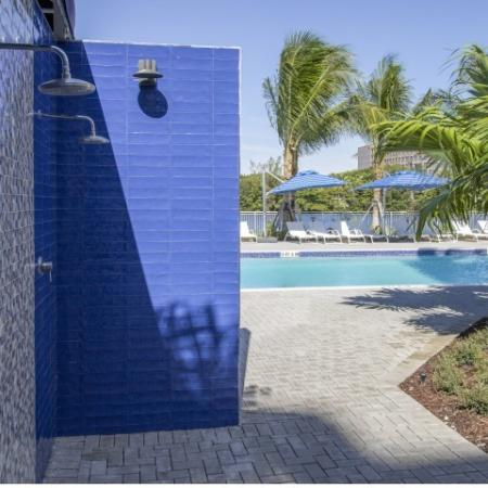 Outdoor shower and swimming pool surrounded by chaise lounges with view of Blue Lagoon Lake.
