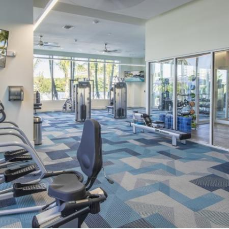 Fitness spin room with stationary bikes, wood flooring, and glass walls