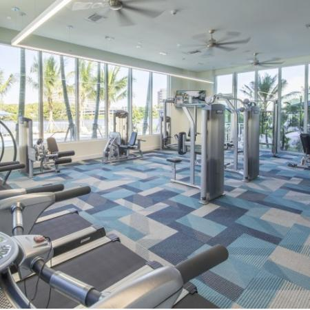 Fitness center with stair master, medicine balls, a separate spin room with glass walls, and various weight machines.