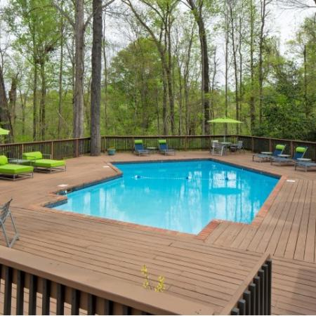 Pool area surrounded by wooden deck, lounge furniture, and forest area