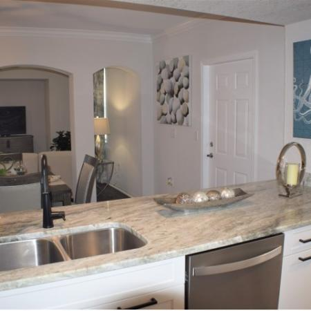 Apartment upgraded kitchen with open bar to dining and living. Upgraded granite with wood like flooring, small island, tiled back splash, upgraded stainless steel appliances, patio door and breakfast nook with windows