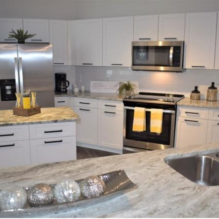 Apartment upgraded kitchen granite with wood like flooring, small island, tiled backsplash, upgraded stainless steel appliances, patio door and breakfast nook with windows