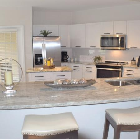 Apartment upgraded kitchen granite with open bar area, wood like flooring, small island, tiled back splash, upgraded stainless steel appliances, patio door and breakfast nook with windows