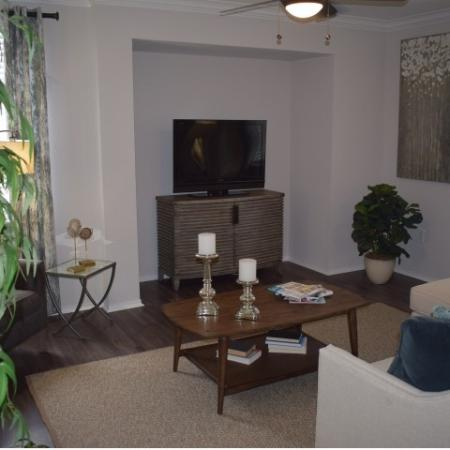 Living room off dining area with wood like flooring, and ceiling fan showing newly renovated open area for TV.
