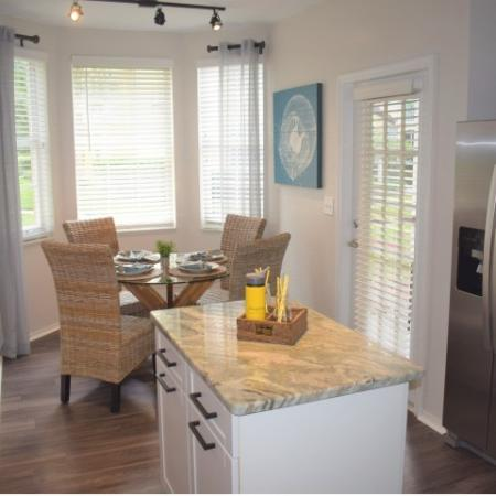 Apartment upgraded kitchen granite with wood like flooring, small island, tiled backsplash, upgraded stainless steel appliances, patio door and breakfast nook with windows.