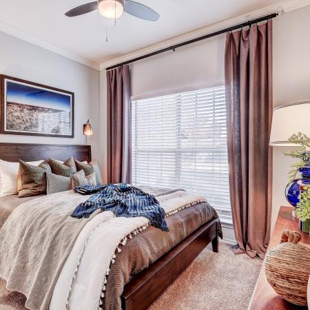 Spacious bedroom large enough to fit a king size bed with luxurious carpet and modern ceiling fan, beautiful natural light.