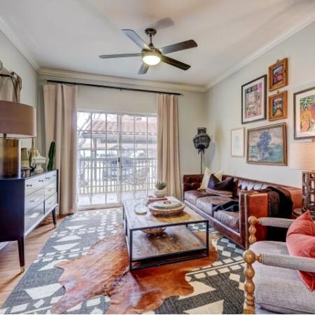 Spacious living room, sliding patio doors, plank wood flooring.