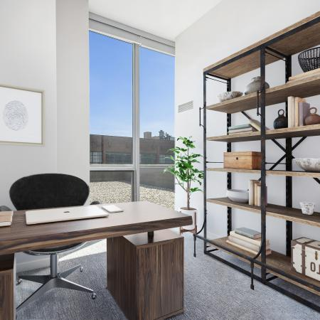 Furnished model bedroom with a desk, shelves and floor-to-ceiling windows with a city view