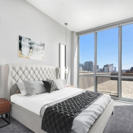 Furnished model bedroom with queen sized bed and floor-to-ceiling windows with a city view