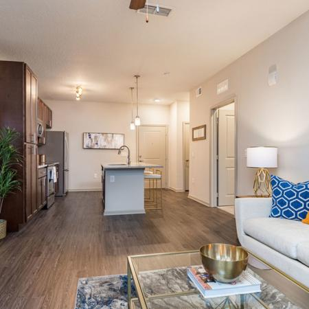 San Mateo Apartments Kissimmee Florida open living area adjacent to kitchen with vinyl plank flooring, wood cabinets, pendant lights, granite counters, and stainless appliances
