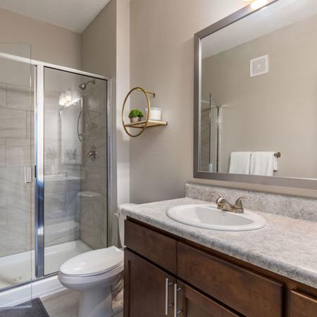 San Mateo Apartments Kissimmee Florida restroom with walk-in shower and framed mirror