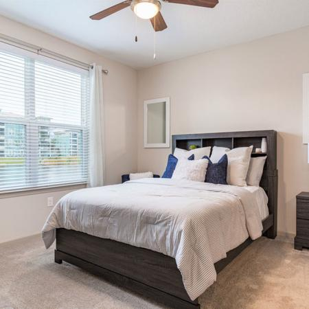 San Mateo Apartments Kissimmee Florida bedroom with carpeted floors and ceiling fan