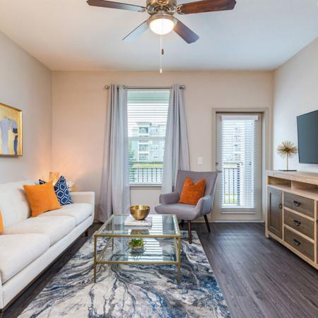 San Mateo Apartments Kissimmee Florida living room with vinyl plank flooring, french patio door, and ceiling fan