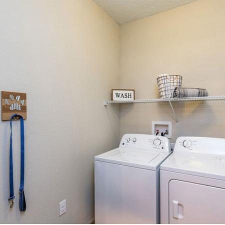 San Mateo Apartments Kissimmee Florida laundry room with full size washer and dryer and storage rack above appliances