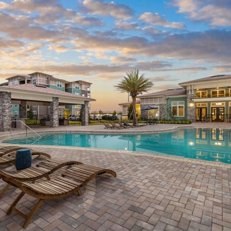 San Mateo Apartments Kissimmee Florida sparkling swimming pool with zero entry and lounge chairs by community clubhouse and outdoor kitchen