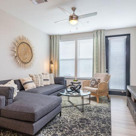 View of furnished model living room area with ceiling fan and patio