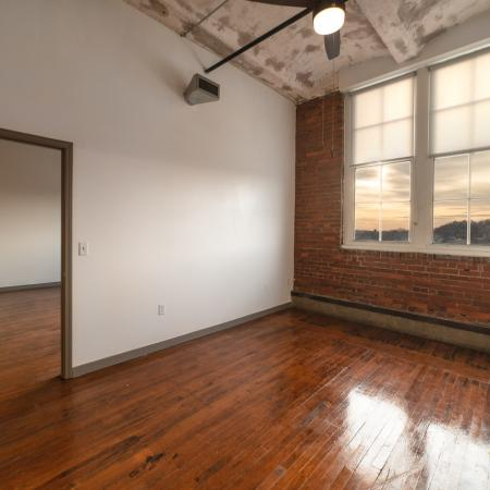 View of empty bedroom with hardwood flooring, exposed concrete ceiling and brick walls