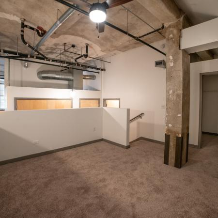 Lofted area with exposed concrete ceiling and carpeted flooring